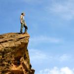 Een afbeelding met een man op een rots