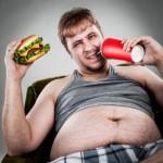 Een dikke man eet en drinkt veel