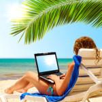 Een vrouw met een laptop op het strand